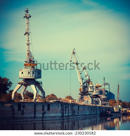 Working cranes for cargo at the shipyard docks in river port, vintage stylized. - stock photo