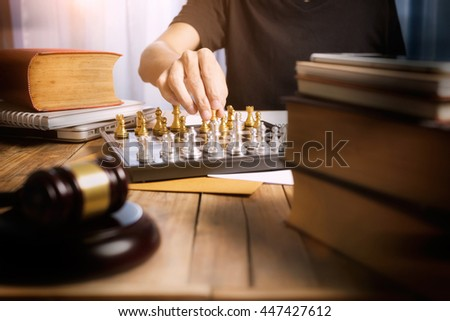 Working desk of lawyer, business man lawyer playing golden chess on his desk, battle and justice concept, front view photography with vintage tone. - stock photo