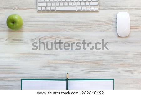 Working desk with green apple. View from above on light beige wooden working desk with green apple, large notepad, computer keyboard and mouse, green pencil - stock photo