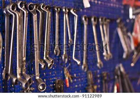 Working desk with the assorted tools hanging at the blue board. - stock photo