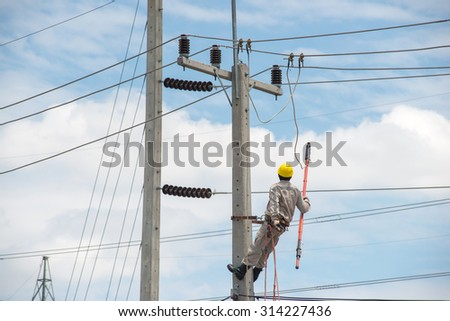 Working engineer on electrical 22 kv pole - stock photo