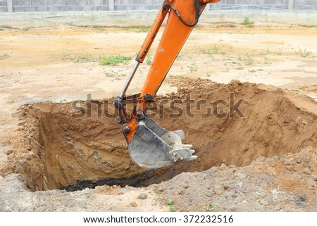 Working excavator backhoe, crop only shovel bucket over the foundation pit.  - stock photo