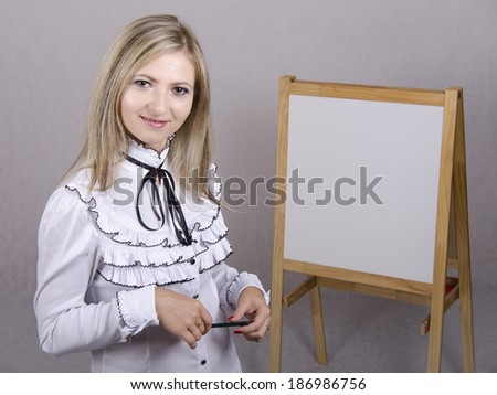 Working girl standing with a pencil in hand. In the background stands the white Board. A girl holds presentation