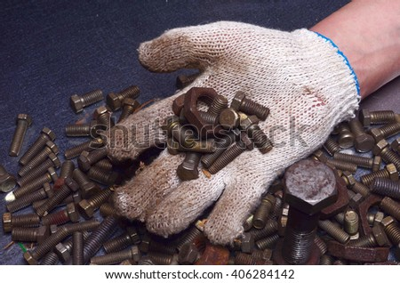 Working Gloves with a Heap of Nuts and Bolts