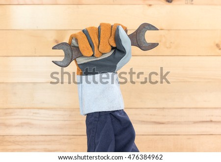 Working hand in glove holding a hammer with wall wood background