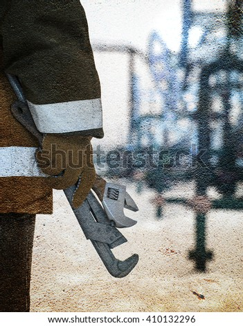 Working hand with wrenches on a wellhead crude oil site background. Petroleum concept. Textured concrete grunge.