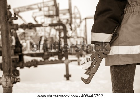 Working hand with wrenches on a wellhead crude oil site background. Toned sepia. - stock photo