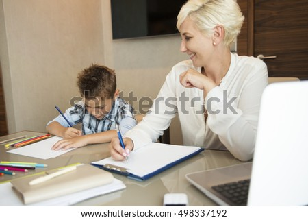 Working home blonde businesswoman with her young son drawing