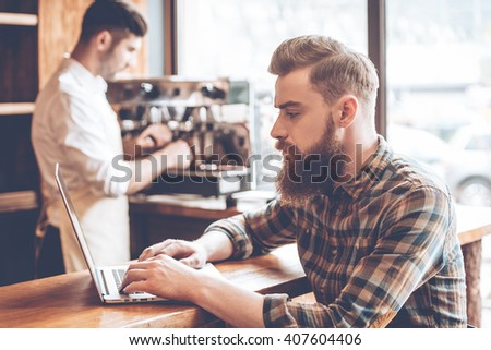 Working in cafe. Side view of young handsome bearded man using his laptop while sitting at bar counter at cafe with barista at the background - stock photo