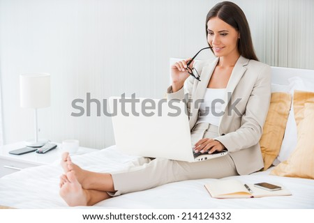 Working in hotel room. Beautiful young businesswoman in suit working on laptop and smiling while sitting in bed at the hotel room - stock photo