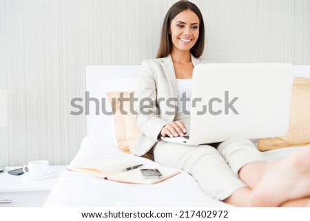 Working in hotel room. Confident young businesswoman in suit working on laptop and smiling while sitting in bed at the hotel room - stock photo
