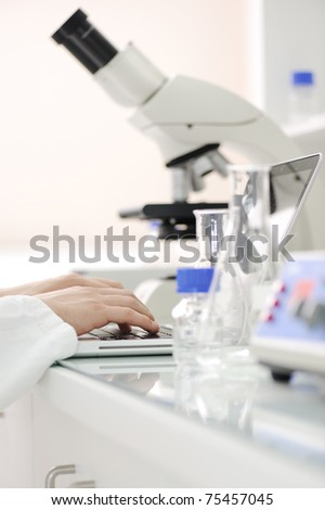 Working in lab with microscope and writing results on laptop, closeup - stock photo
