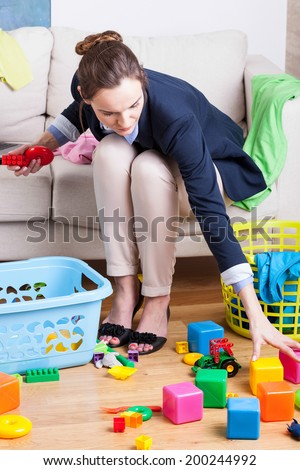 Working lady cleaning up colorful kids toys  - stock photo