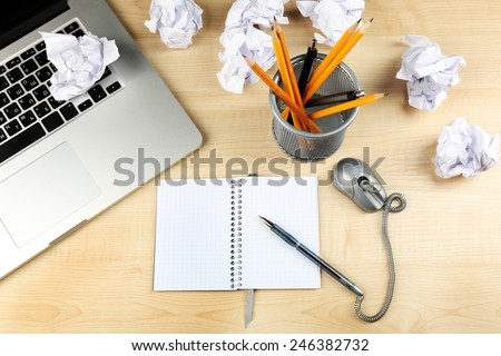 Working mess with crumpled paper and notebook on wooden table background - stock photo