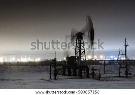 Working oil pump jack at night time. Oilfield during winter. Refinery lights background. Oil and gas concept. Motion blur. Toned.