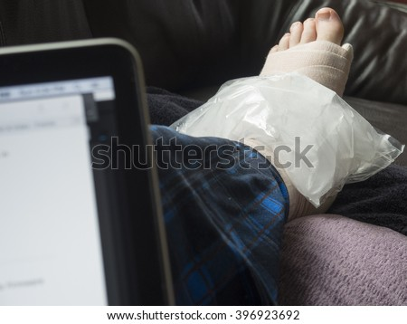 Working on a Computer While Icing an Injured Foot Which Is Broken, Fractured, or Sprained - stock photo