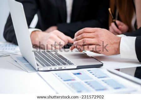 Working on a laptop. Four successful businessman sitting at the table at a business meeting in the office. Close-up of hands - stock photo