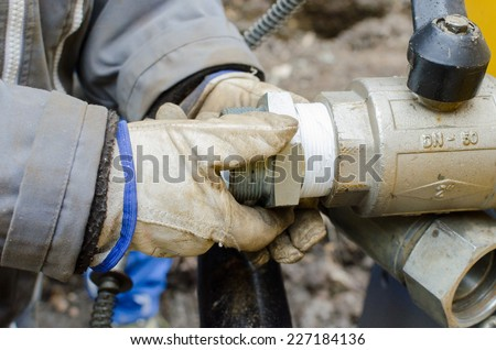 Working on a pipe connector with protective gloves - stock photo