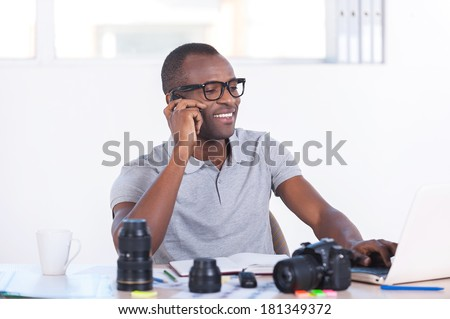 Working on creative project. Handsome young African man in casual wear sitting at his working place and talking on the mobile phone - stock photo