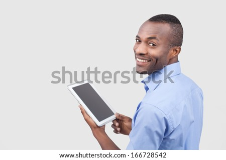 Working on digital tablet. Rear view of young African man working on digital tablet and looking over shoulder while standing isolated on grey - stock photo