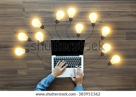 Working on laptop computer PC with creative light bulb ideas, View from above