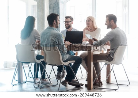 Working on new project together. Group of confident business people in smart casual wear working together while sitting at the desk in office