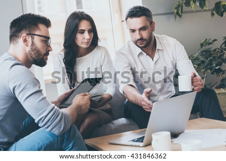 Working on project together. Confident young man pointing laptop while sitting together with his colleagues in office  - stock photo