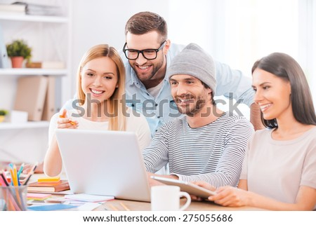 Working on project together. Group of cheerful business people in smart casual wear sitting together at the wooden desk and looking at laptop - stock photo