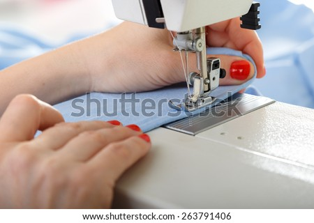 Working on sewing machine. Close look of hands and needle - stock photo