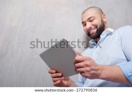 Working on tablet computer. Handsome young arabic man working on digital tablet while leaning on grey wall. - stock photo