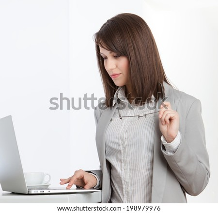 Working on the computer businesswoman at the office, isolated on white - stock photo
