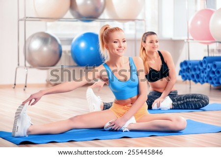 Working out and feeling amazing. Two beautiful young women in sports clothing exercising together and smiling while stretching against pilates balls - stock photo
