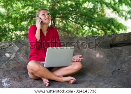 working outdoors - beautiful suntanned 20s girl laughing on cell phone with laptop on crossed legs in shape of trees sitting on giant stone,natural daylight - stock photo