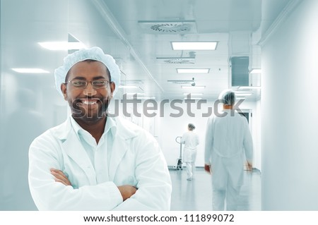 Working people with white uniforms in modern  facility - stock photo