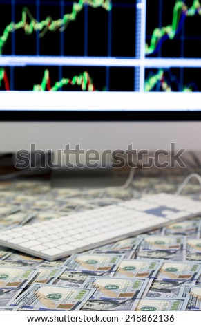 Working place of investor. The table covered by cash notes, keyboard and financial charts on the computer screens - stock photo