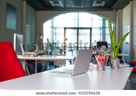Working Place on grey Table with Laptop Computer green Flower red Chair and Pencils in modern Office interior with large Window on Background - stock photo