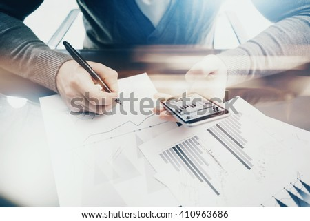 Working process. Account manager working at the table with new business project.Holding modern smartphone hand, statistics screen. Signs document, analyze plans. Horizontal,visual and film effect