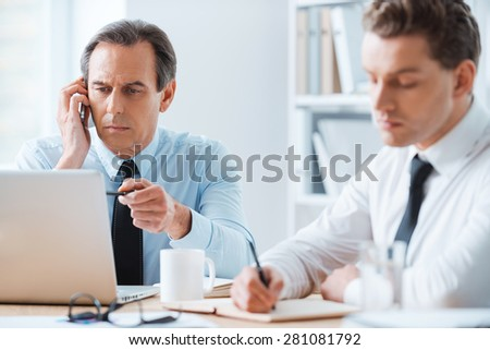 Working process. Serious businessman talking on the mobile phone and pointing at the laptop while another businessperson writing something in note pad - stock photo