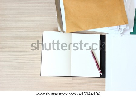 working supplies,notepad,pencil,paper on wood background