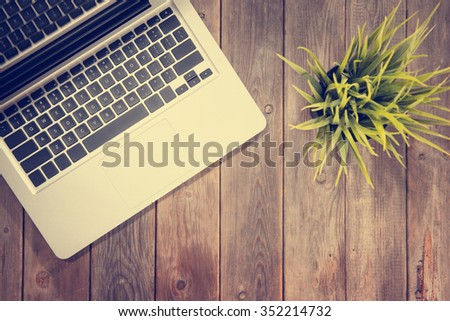 Working table with laptop computer and plant pot. Wooden table background with copy space on bottom. Instant photo vintage split toning color effect. - stock photo