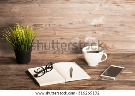 Working table with notepad, coffee cup , pen , smartphone , glasses, plant pot. Wooden table background with copy space on top. Soft focus with noise. Instant photo vintage split toning color effect. - stock photo