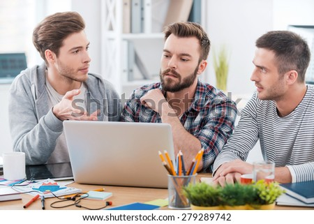Working through it together. Three young men working together while sitting at their working place in office - stock photo