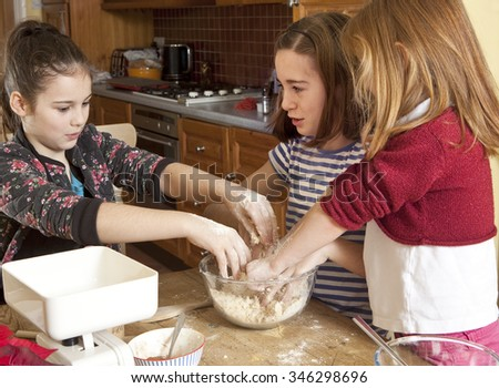 Working Together. Three sisters are working together to make gingerbread for Christmas presents. They are rubbing the butter into the flour to make a bread crumb texture.