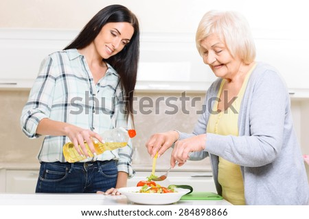 Working together. Two women of different generations standing in kitchen and cooking salad. - stock photo