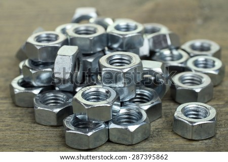 Working tools. Fixing elements (nuts) on wooden background - stock photo