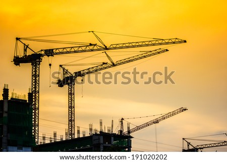Working tower crane at late evening in silhouette.