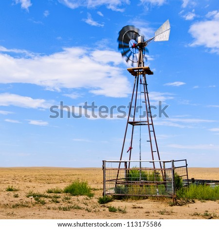 Working windmill providing drinking water for cattle - stock photo