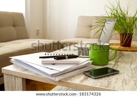 Working with a pile of papers and a laptop  - stock photo