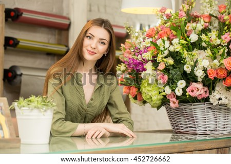 Working with flowers. Portrait of a gorgeous young florist leaning on a counter at her own flower shop smiling cheerfully  - stock photo