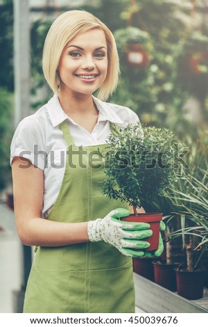 Working with plants. Beautiful young woman in apron holding a potted plant and smiling while standing in a greenhouse - stock photo